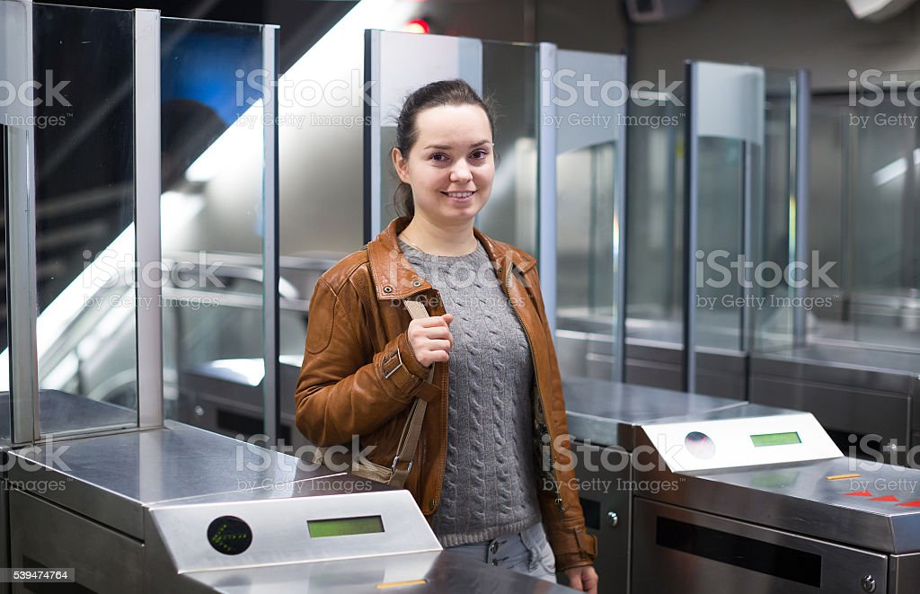Girl passing ticket barrier in subway stock photo