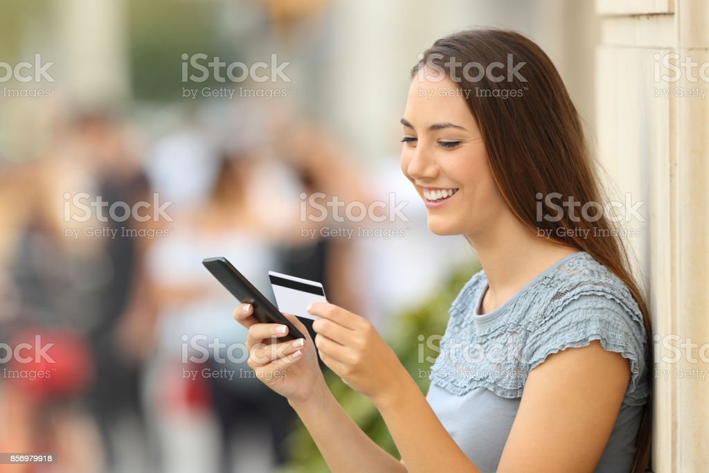 Girl paying on line with a credit card and phone - foto stock