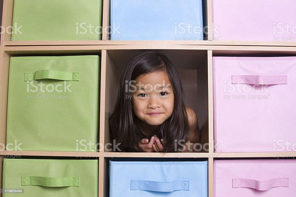 Girl peeking through cubed shelving unit royalty-free stock photo