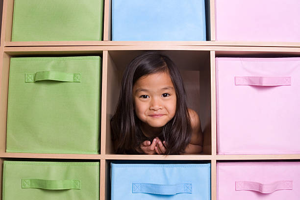 Girl peeking through cubed shelving unit Playful Chinese little girl peeking through colorful shelving unit girl bedroom stock pictures, royalty-free photos & images