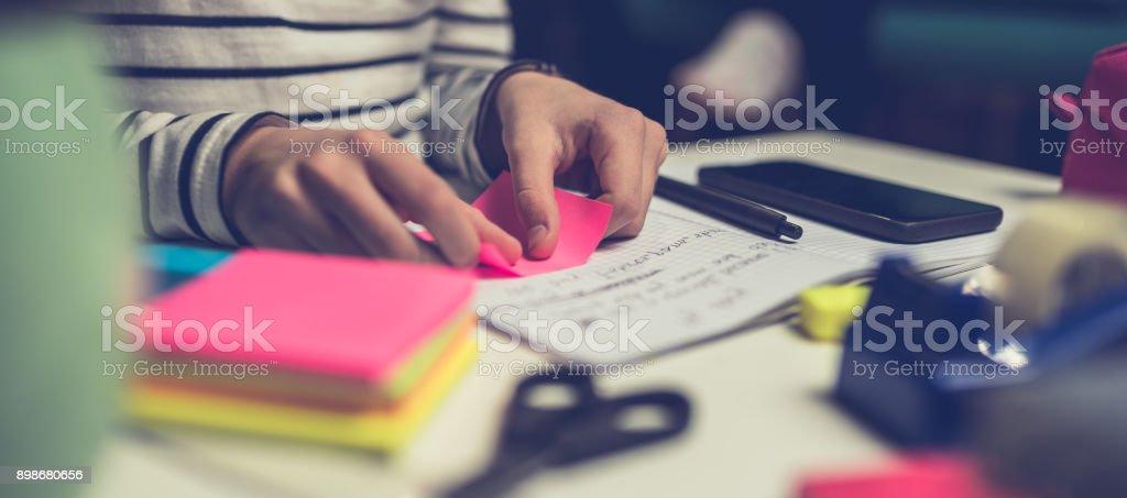 Girl peeling off sticky notes stock photo
