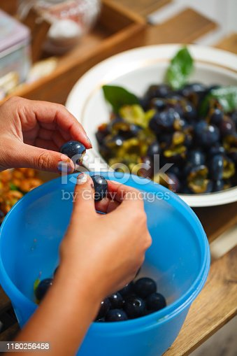 Woman's hands peel plums to make jam or chutney