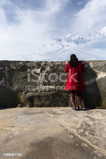 Girl peering over stone fence in red jacket wondering what's on the other side of the wall.
