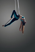 Sporty woman doing exercise with elastics, aerial straps ribbons, aerial tissues . Sport training gym and lifestyle concept. Anti-gravity yoga.