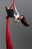 Sporty woman doing exercise with elastics, aerial silk ribbons. Sport training gym and lifestyle concept. Anti-gravity yoga.
