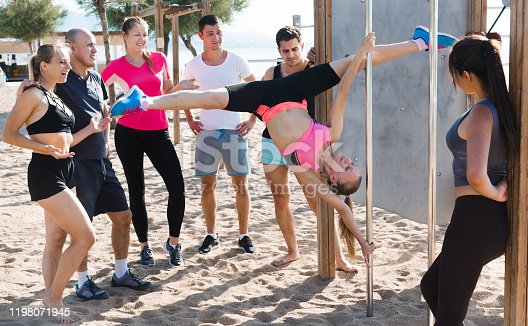 Sporty girl performing pole exercises causing admiration of people watching her