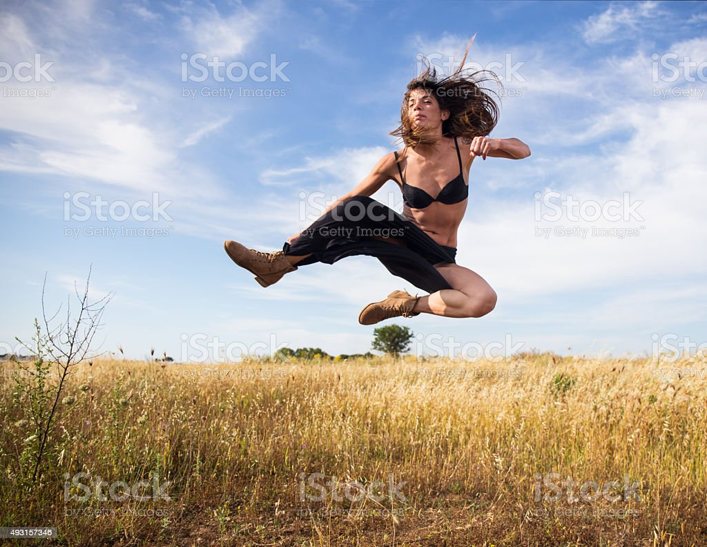 Girl performs a flying kick in a campaign stock photo