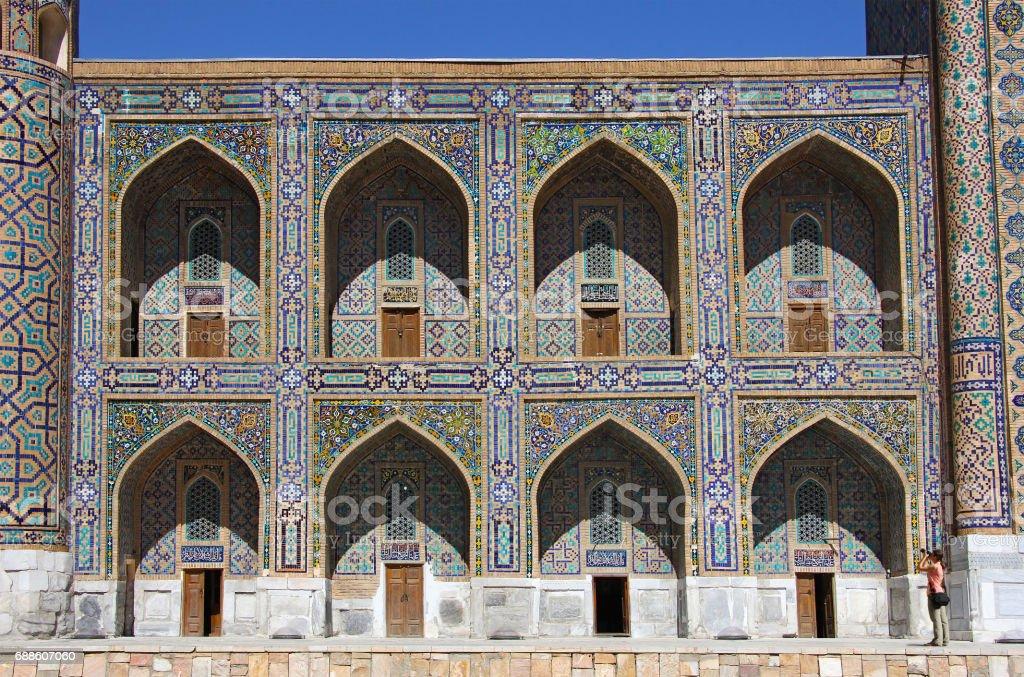 girl photographer in front of the west wing of Tilya-Kori Madrasah, Registan square, Samarkand stock photo