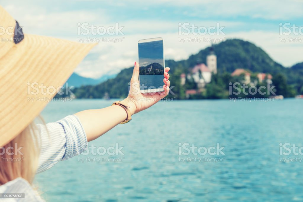 Girl photographing nice scenery on the lake. stock photo