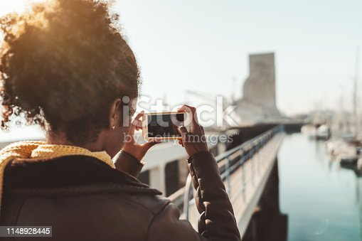 View from behind of a curly-hair female in leather demi-season coat photographing in a landscape mode a cityscape with quayside, buildings, yachts, and boats using the camera of her smartphone