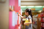 本棚で本を選ぶ少女