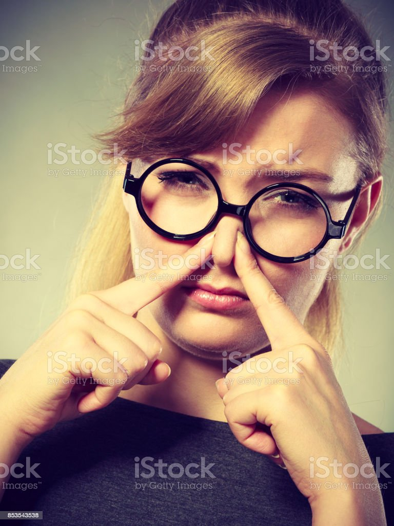 Girl pinches her nose because of stench stink. stock photo