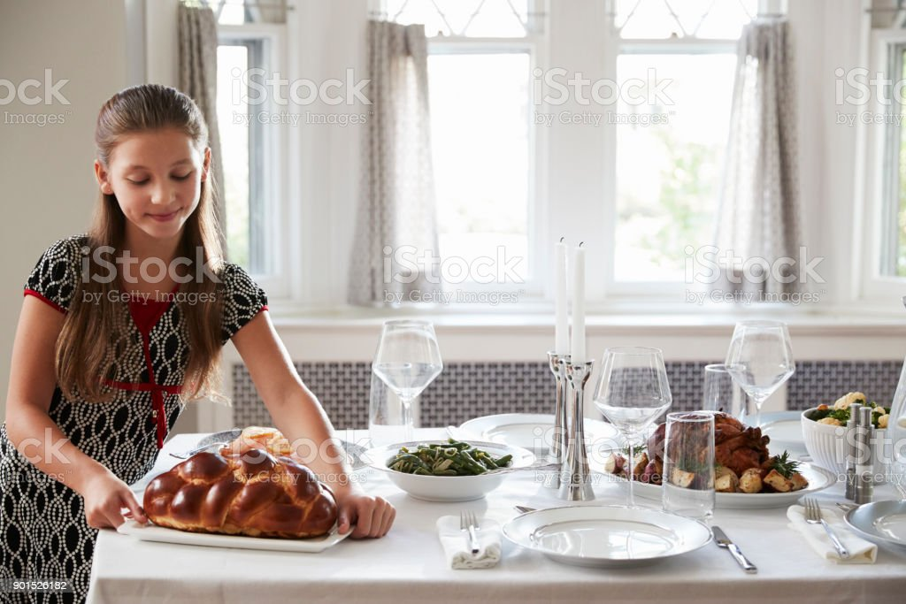 Girl placing challah bread on a table for Shabbat meal stock photo