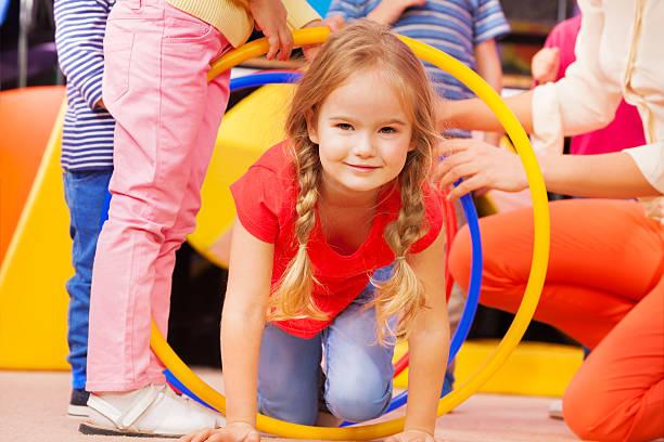 mädchen spielen in bereits im kindergarten crawl obwohl hoop - hula hoop workout stock-fotos und bilder