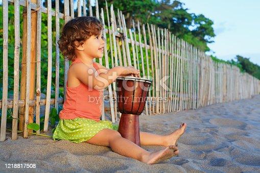 182677415 istock photo Girl play ethnic music on traditional african hand drum djembe 1218817508