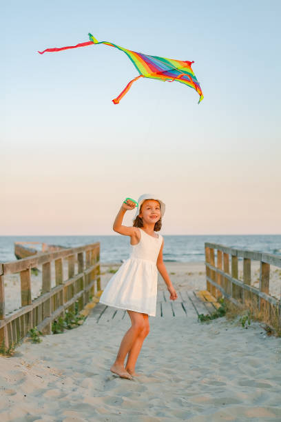Girl play with rainbow colorful kite on the beach at sunset stock photo
