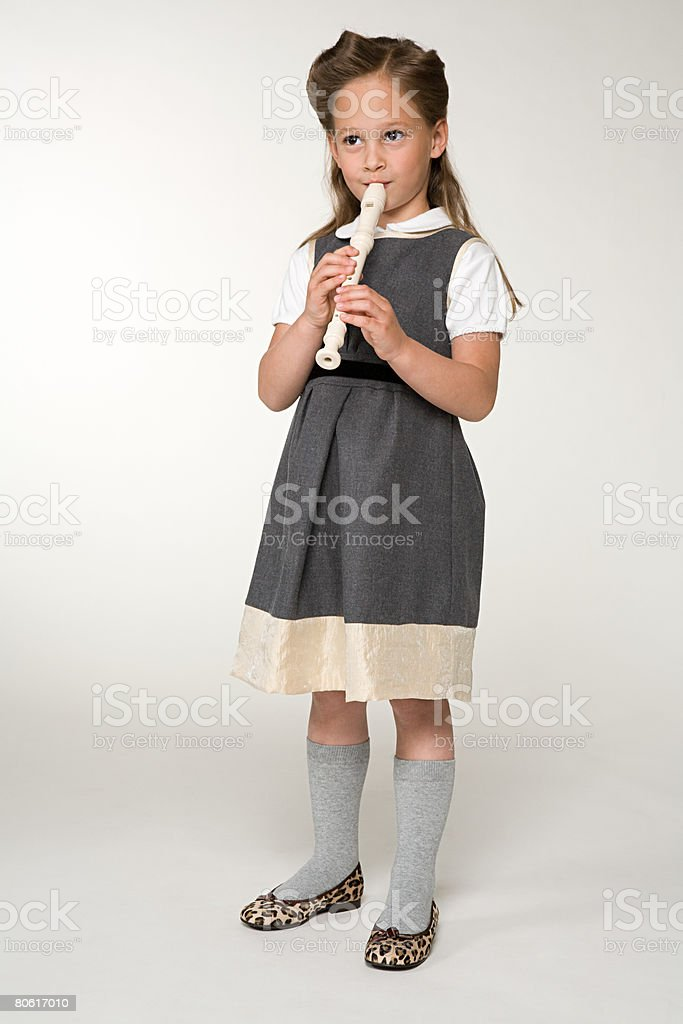 A girl playing a recorder royalty-free stock photo