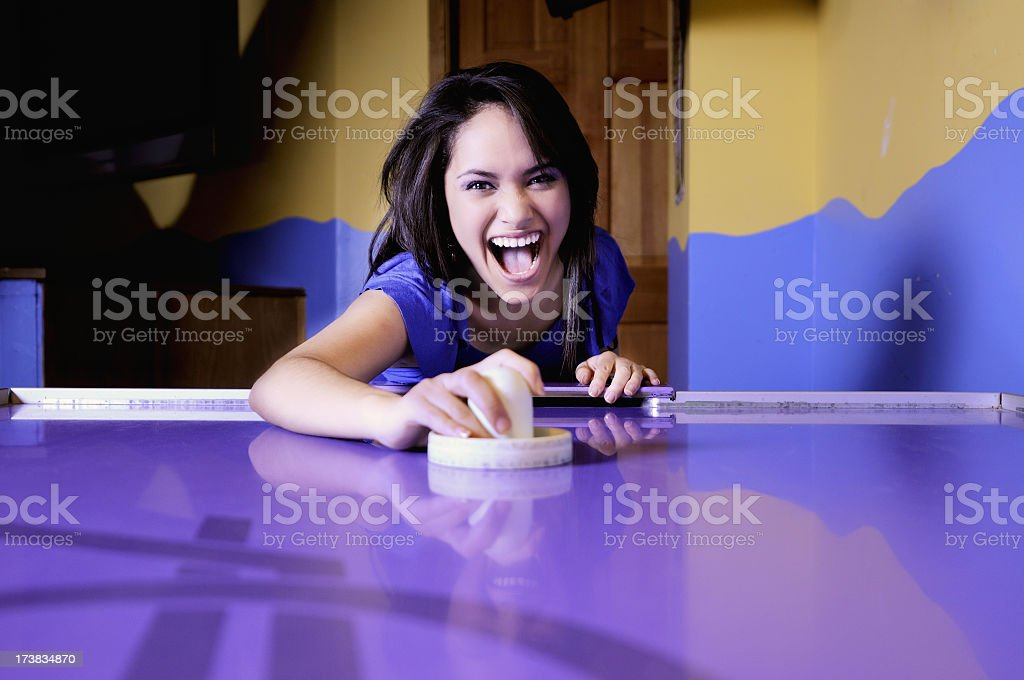 Girl playing air hockey in a purple table stock photo
