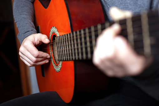istock girl playing an acoustic guitar. string musical instrument guitar 1208067518