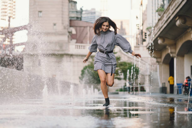 girl playing and dancing around on a wet street stock photo