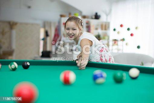 Girl playing billiards.Daughter playing pool