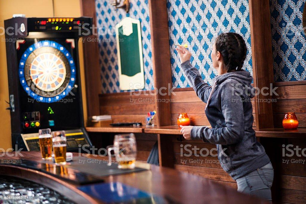 Girl playing darts at bar stock photo