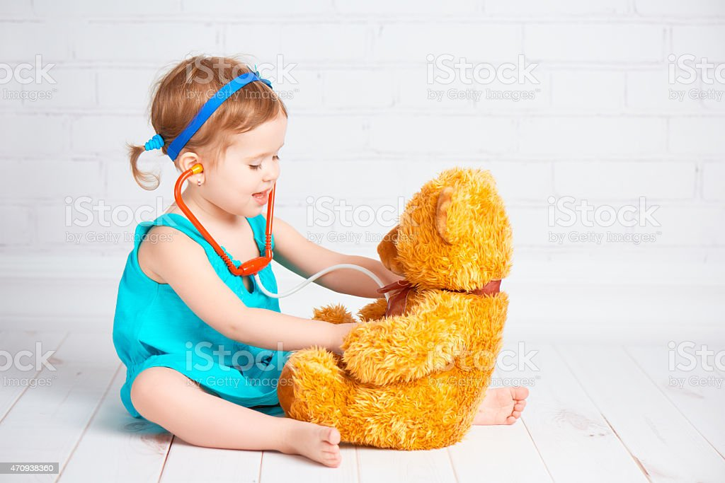 girl playing doctor and treats teddy bear stock photo