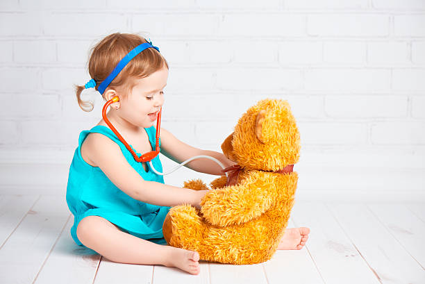 girl playing doctor and treats teddy bear stock photo