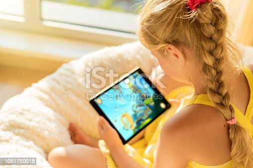 Unrecognizable girl playing game on tablet computer