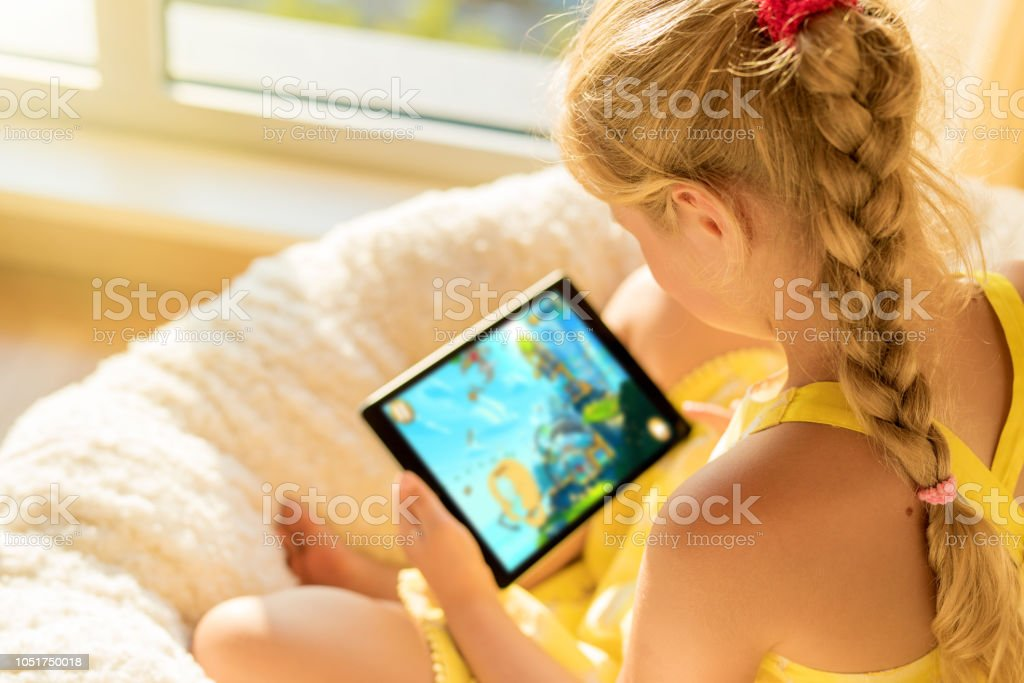 Girl playing game on tablet computer stock photo
