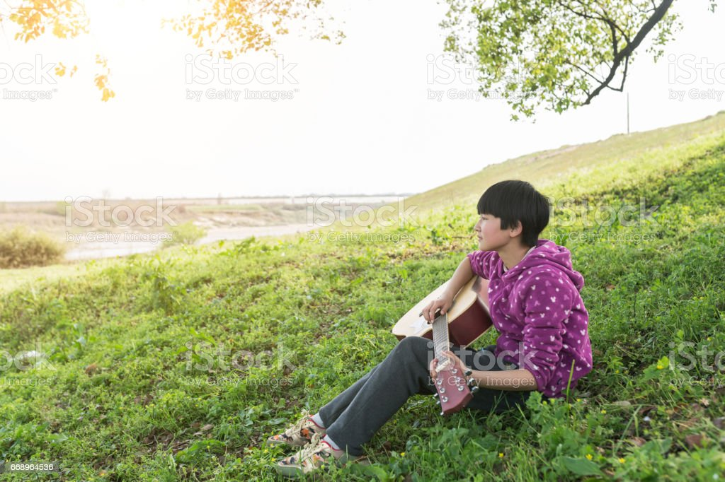 girl playing guitar at outdoor foto stock royalty-free