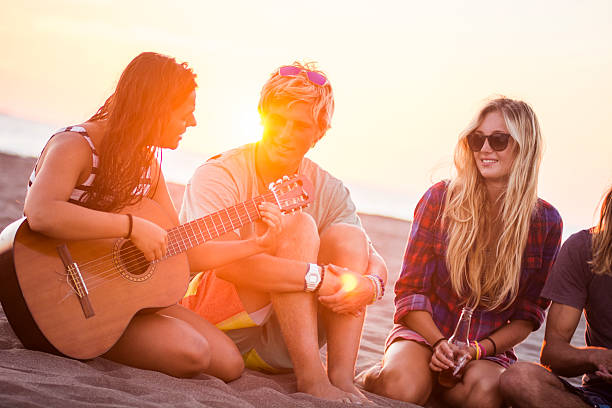 Girl playing guitar at the beach stock photo