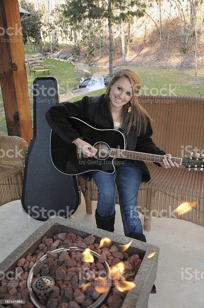 Girl playing guitar by fire in park royalty-free stock photo