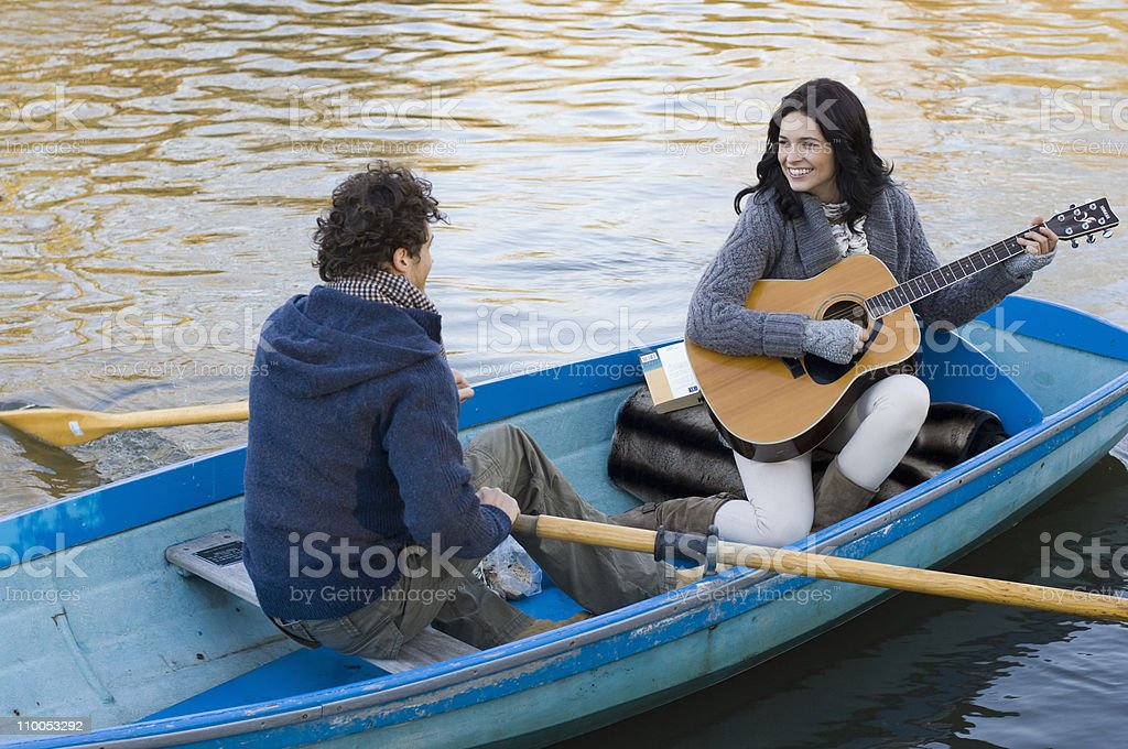 Girl playing guitar in row boat stock photo
