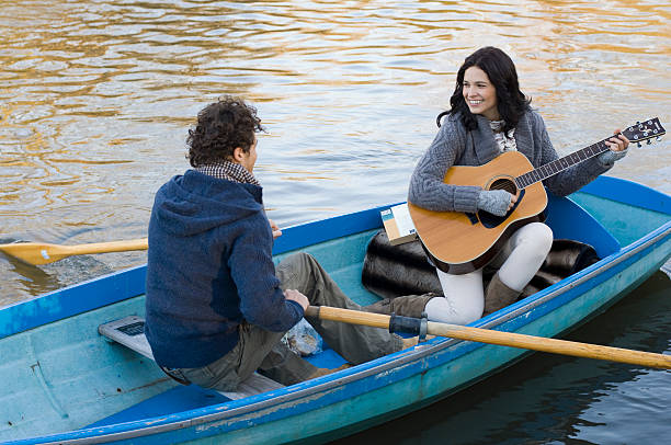 Girl playing guitar in row boat  serenading stock pictures, royalty-free photos & images
