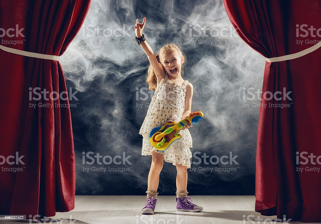 girl playing guitar on stage stock photo