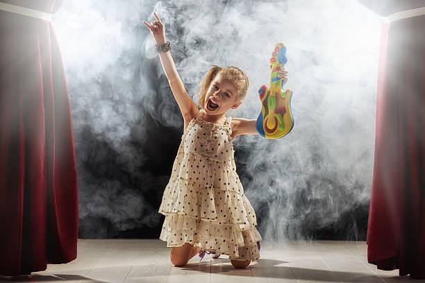 girl playing guitar on stage - mädchen vorhänge stock-fotos und bilder