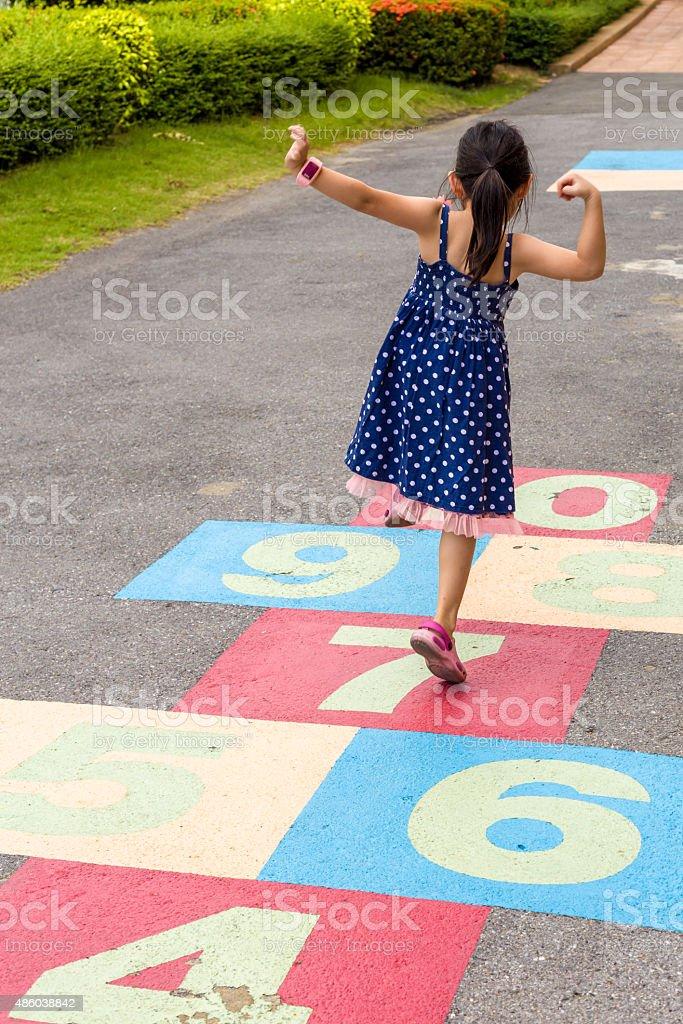 Girl Playing Hopscotch / Girl Playing Hopscotch on Playground stock photo