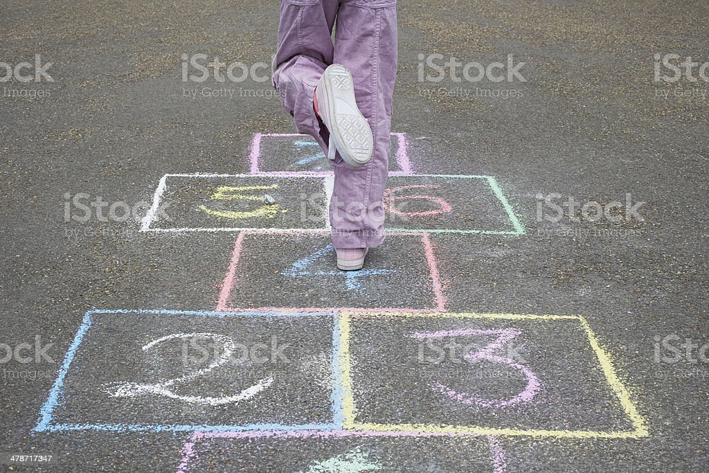 Girl Playing Hop-Scotch In Playground stock photo