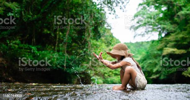 Photo of Girl playing in a mountain stream