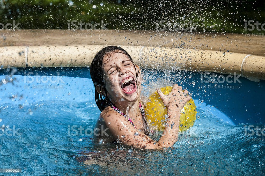 Girl playing in a swimming pool royalty-free stock photo