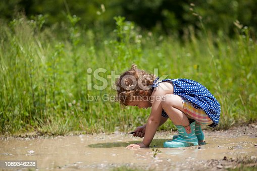 Side view of girl playing in muddy water.