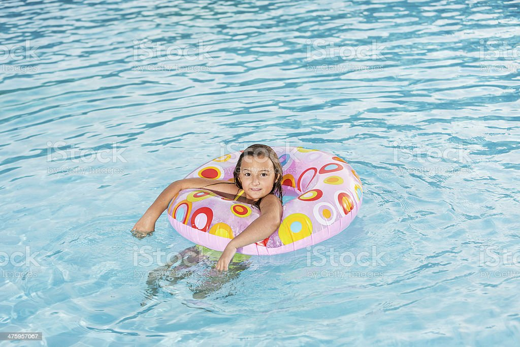 Girl playing in swimming pool. stock photo