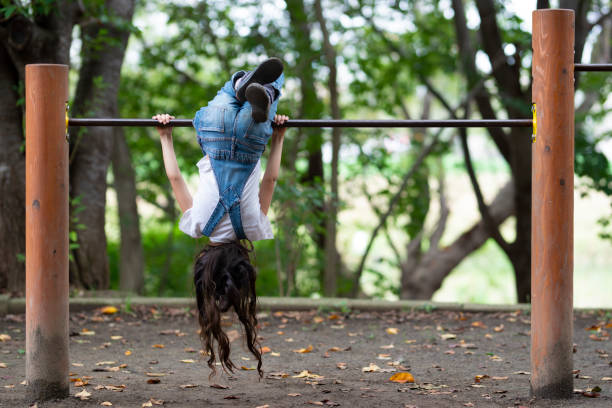 girl playing in the park - horizontal bar stock photos and pictures