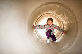 Little girl going through concrete tunnel while playing in the park.