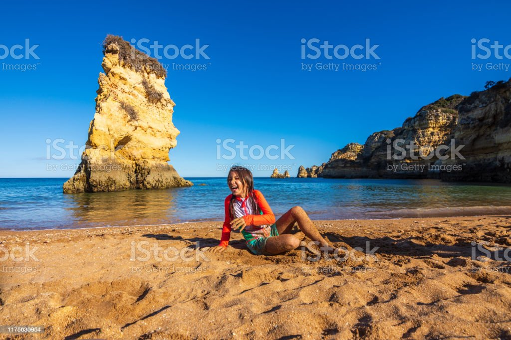 Girl playing in the sand of Praia Dona Ana beach in Algarve, Portugal - Royalty-free 8-9 Years Stock Photo