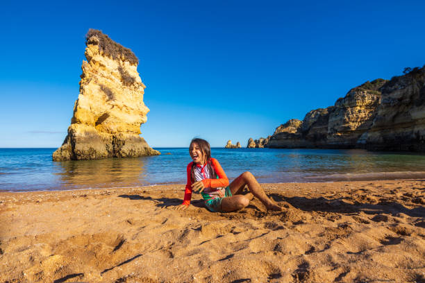 Girl playing in the sand of Praia Dona Ana beach in Algarve, Portugal stock photo