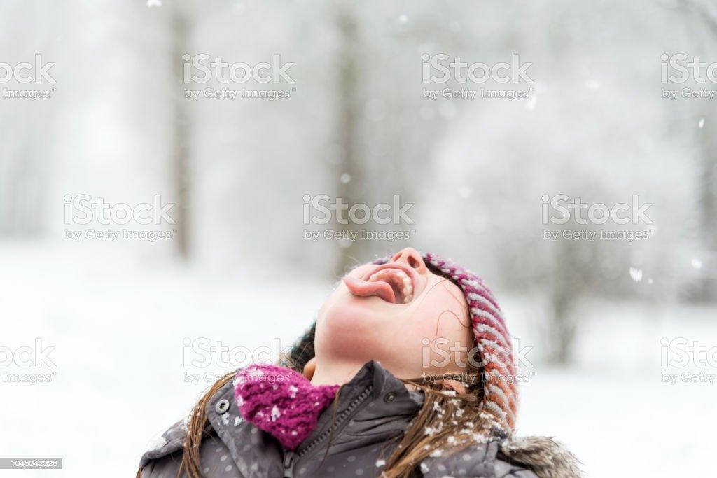 Mädchen spielen im Schnee - versucht es, Schneeflocken mit ihrem Mund zu fangen – Foto