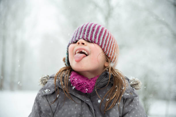 Girl playing in the snow - it tries to catch snowflakes with her mouth stock photo