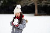 雪の降る公園で遊ぶ女の子